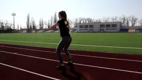 La mujer activa del ajuste atractivo joven que hace posiciones en cuclillas calienta la elaboración al aire libre de los músculos almacen de video