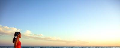 La mujer activa en deportes adapta en la costa en caminar de la puesta del sol Imagen de archivo