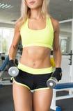 La mujer activa en ropa verde atlética se involucra con una pesa de gimnasia en el gimnasio Fuerza de la voluntad Carrocería herm Fotografía de archivo libre de regalías