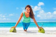 La mujer activa que hace deportes ejercita con los cocos en la playa del mar foto de archivo libre de regalías