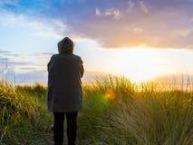 La mujer admite el momento efímero de la puesta del sol imagenes de archivo