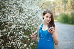 La mujer adolescente escucha la música en su smartphone en parque Imágenes de archivo libres de regalías
