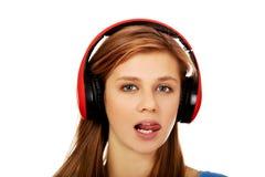 La mujer adolescente escucha la música y muestra el tounge Imagen de archivo libre de regalías