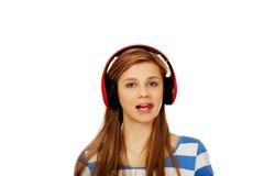 La mujer adolescente escucha la música y muestra el tounge Fotos de archivo