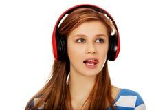 La mujer adolescente escucha la música y muestra el tounge Imágenes de archivo libres de regalías