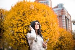 La mujer adolescente feliz que escucha la música y se relaja en parque del otoño Árboles amarillos, tiempo de caída hermoso Fotografía de archivo