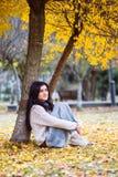 La mujer adolescente feliz que escucha la música y se relaja en parque del otoño Árboles amarillos, tiempo de caída hermoso Fotos de archivo