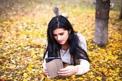 La mujer adolescente feliz se relaja en parque del otoño Árboles amarillos, tiempo de caída hermoso Imagen de archivo libre de regalías