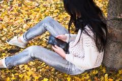 La mujer adolescente feliz se relaja en parque del otoño Árboles amarillos, tiempo de caída hermoso Foto de archivo libre de regalías