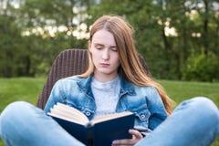 La mujer adolescente leyó el libro afuera Fotografía de archivo libre de regalías