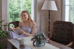 La mujer adolescente leyó el libro dentro Foto de archivo libre de regalías