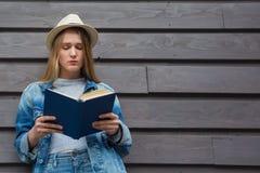 La mujer adolescente leyó el libro fuera de la pared Foto de archivo