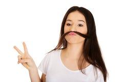 La mujer adolescente que pone el pelo le gusta el bigote Fotografía de archivo libre de regalías