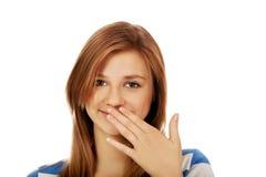 La mujer adolescente ríe nerviosamente cubriendo su boca con la mano Fotos de archivo