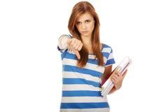 La mujer adolescente sosteniendo los libros y las demostraciones manosean con los dedos abajo Fotos de archivo libres de regalías