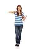 La mujer adolescente sosteniendo los libros y las demostraciones manosean con los dedos abajo Imagenes de archivo