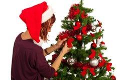 La mujer adorna el árbol con las cintas Imagenes de archivo