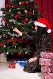 La mujer adorna el árbol de navidad Imagen de archivo libre de regalías