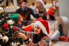 La mujer adorna el árbol de navidad para la Nochebuena Imagenes de archivo