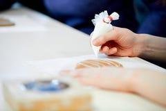La mujer adorna el pan de jengibre fotografía de archivo libre de regalías