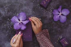 La mujer adorna el presente con las flores de la orquídea Foto de archivo libre de regalías