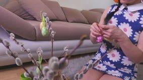 La mujer adorna el sauce de gatito con los huevos de Pascua