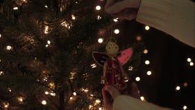 La mujer adorna la guirnalda de hadas en un árbol de navidad con el fondo de las luces del bokeh de la iluminación almacen de video
