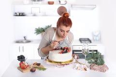 La mujer adorna la torta con la fruta Fotografía de archivo