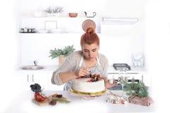 La mujer adorna la torta con la fruta Fotos de archivo