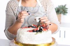La mujer adorna la torta kanduriny Imágenes de archivo libres de regalías