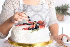 La mujer adorna la torta kanduriny Imagenes de archivo