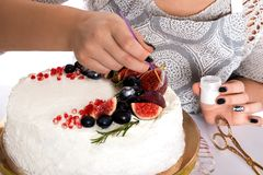 La mujer adorna la torta kanduriny Fotografía de archivo libre de regalías