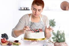La mujer adorna la torta kanduriny Imagen de archivo