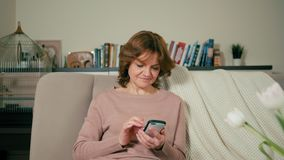 La mujer adulta agradable está utilizando el app en el smartphone que se sienta en el sofá en un cuarto acogedor almacen de metraje de vídeo