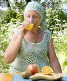 La mujer adulta bebe el zumo de naranja fresco Imagenes de archivo