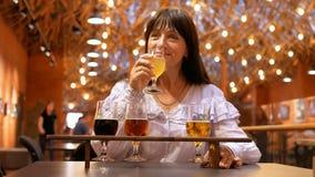 La mujer adulta bebe varias clases de cerveza en una institución interesante El ama de casa pasa su consumición del tiempo libre almacen de video