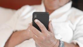 La mujer adulta desconocida en la albornoz blanca en hotel utiliza smartphone El concepto de usar tecnología y los artilugios cer almacen de video