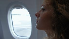 La mujer adulta elegante se está sentando dentro de un avión, mirando en porta en un cielo azul claro y mensajes que mandan un SM almacen de video