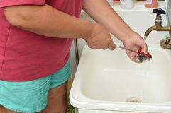 La mujer adulta en pantalones cortos y una camiseta lavan el cuchillo debajo de la agua corriente al aire libre Fotografía de archivo libre de regalías