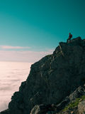 La mujer adulta entonada de la imagen con una mochila se opone al borde de un acantilado y de mirar la salida del sol al cielo az Fotografía de archivo