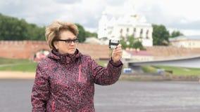 La mujer adulta envejeció 60s toma las fotos usando smartphone almacen de video