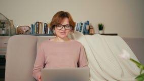 La mujer adulta está llamando con vídeo vía webcam en ordenador portátil y está saludando a mano la onda almacen de video