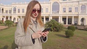 La mujer adulta está mecanografiando el mensaje importante en smartphone, mira en el reloj en la calle almacen de metraje de vídeo