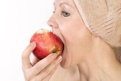 La mujer adulta está mordiendo una manzana. Imagen de archivo libre de regalías