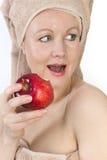 La mujer adulta está mordiendo una manzana. Imagen de archivo