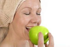 La mujer adulta está mordiendo una manzana. Foto de archivo