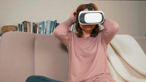 La mujer adulta está poniendo en los vidrios de la realidad virtual que se sientan en el sofá en casa metrajes