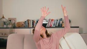 La mujer adulta está utilizando los vidrios de VR con los brazos aumentados que intentan tocar los objetos 3D metrajes