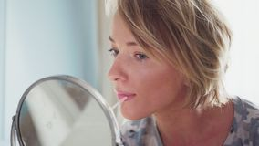 La mujer adulta hace el maquillaje que aplica el lápiz labial almacen de metraje de vídeo