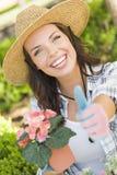 La mujer adulta hermosa da los pulgares para arriba que cultiva un huerto al aire libre Fotos de archivo